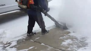 Picture of a man clearing snow with a backpack blower and an AirJet shovel