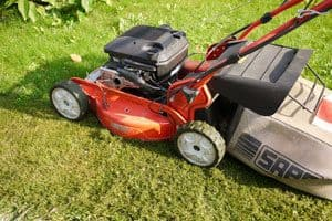 Picture of a lawn mower with grass clippings on its wheels